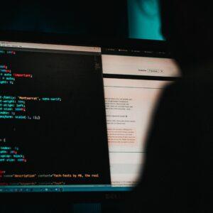 Shadowy figure reading html on dark computer screen